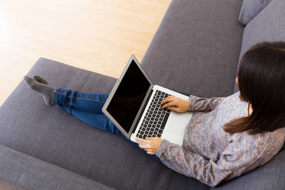 Woman using laptop computer on sofa